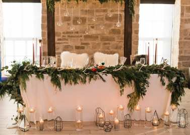 fresh look design head table with greenery and candles