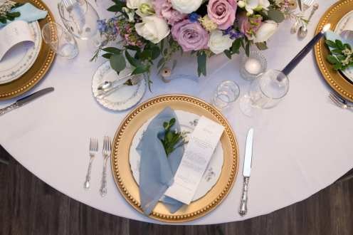 fresh look design wedding place setting with gold charger plate and pink and lavender floral centrepiece