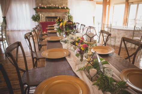 fresh look design long wedding table with white draped runner, greenery flowers and gold charger plates, wooden ladder back chairs