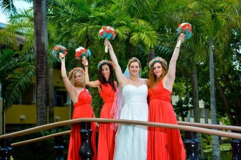 Bridesmade bride with there bridesmaids dressed in long red dresses and flower crowns