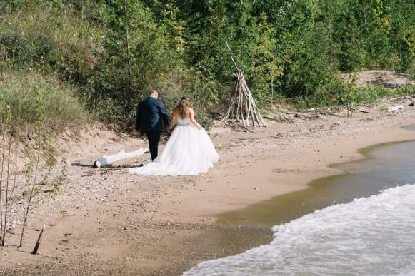 bride and groom walking down Hessenland's private beach