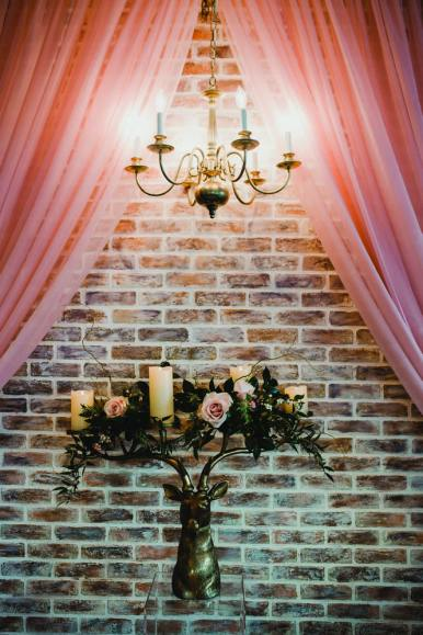 wedding decor in brick, rose and gold candles flowers and chandelier