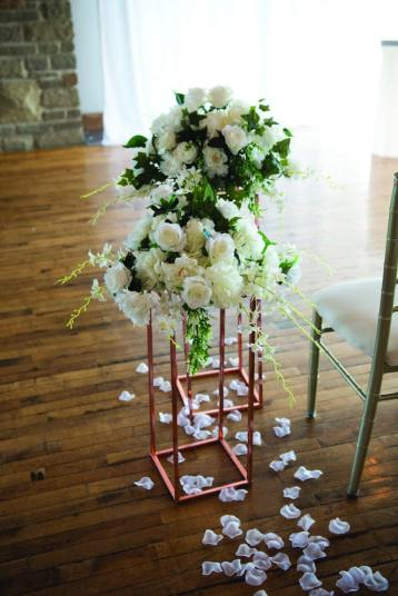 beautiful floral arrangement with white flowers and greenery sitting on top of a copper pipe stand