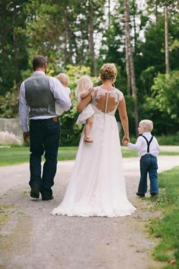 Creme Couture bride and groom walking with children