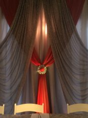 Now & Always wedding backdrop broach in gold on red fabric