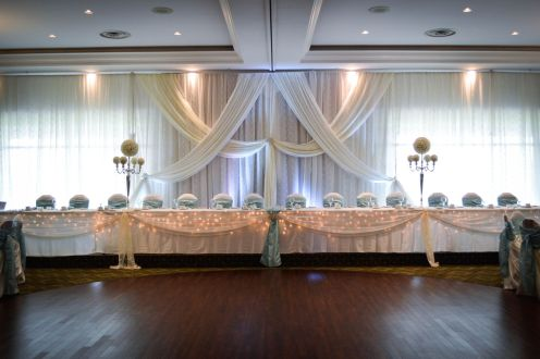 Now & Always head table backdrop with white draping, floral balls and candelabras