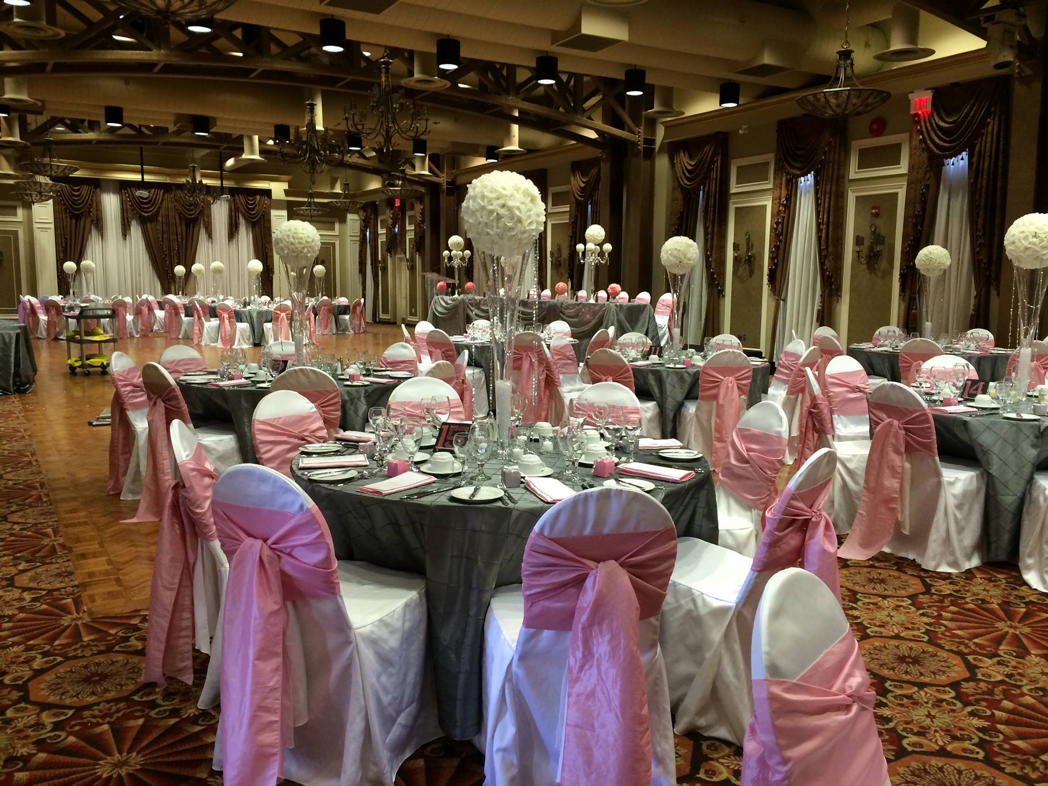 Now & Always pink sashes on white chair covers with tall wedding centrepieces