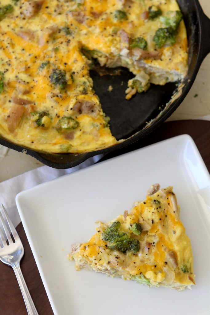 overhead shot of a slice of healthy broccoli cheddar chicken frittata on a plate with a skillet in the back