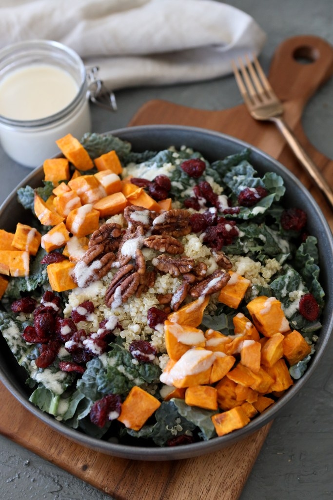 overhead shot of a healthy harvest bowl with kale, roasted sweet potatoes, cranberries and pecans