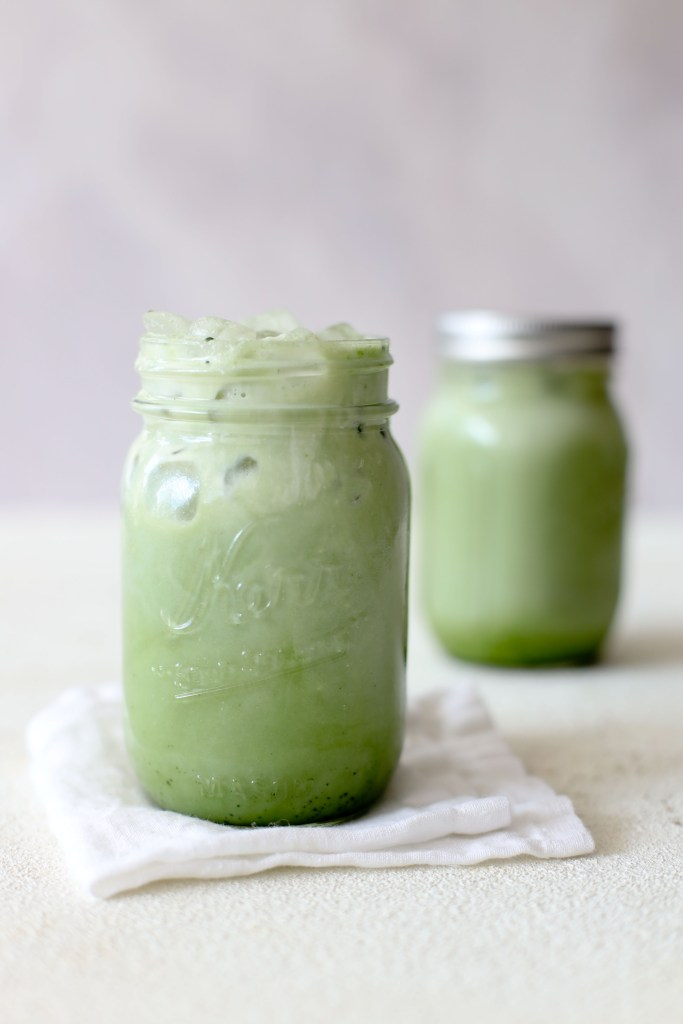 two mason jars with healthy dairyfree matcha lattes on a white table