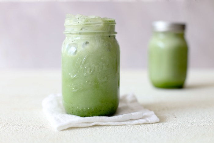 two mason jar matcha lattes on a white table