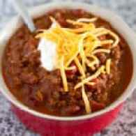 The best classic chili recipe in a red bowl topped with cheddar cheese and sour cream