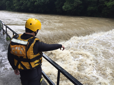 A rescue worker points at a swollen river