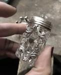 silver poison perfume bottle