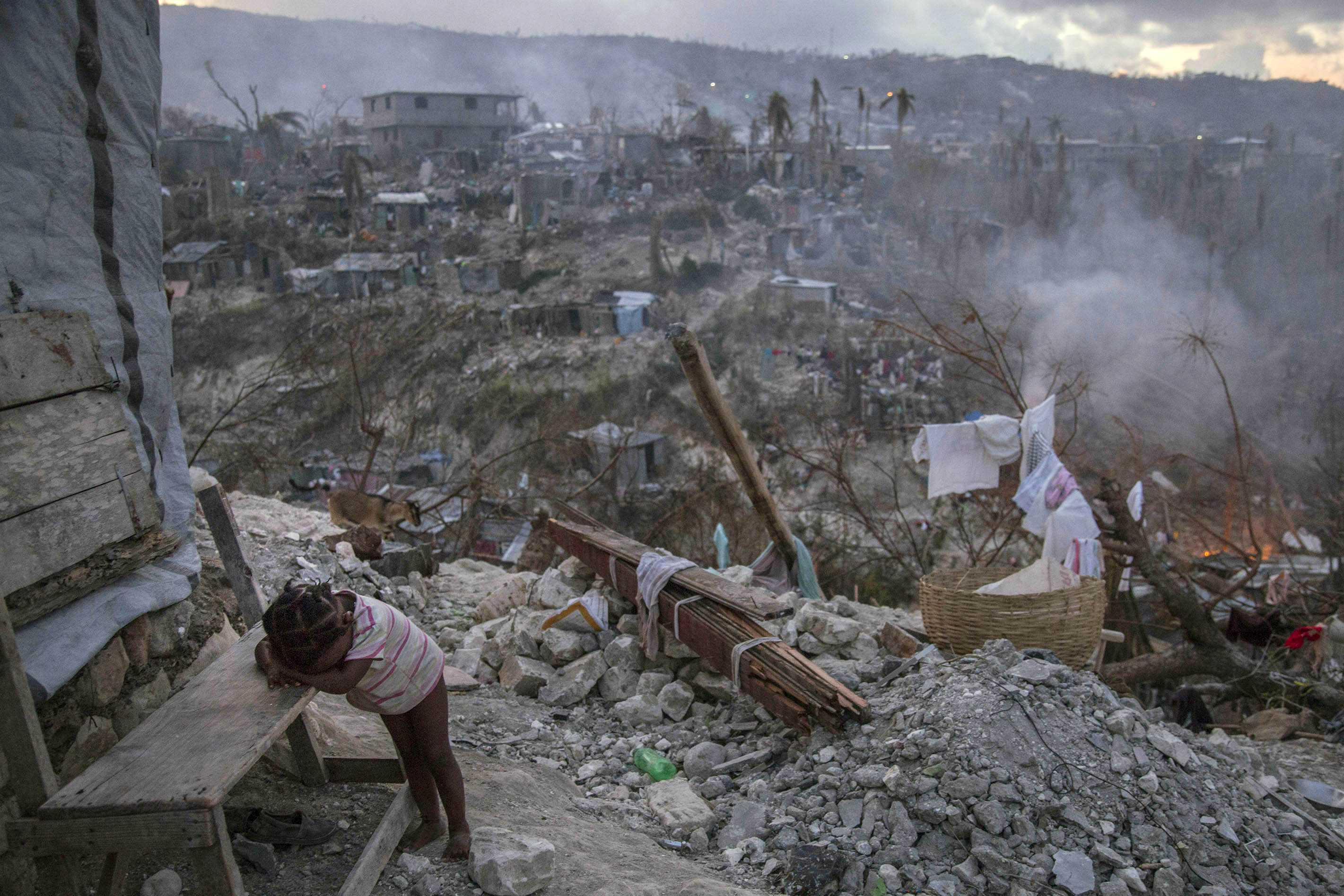 On 10 October 2016 in Jérémie, Haiti, a toddler rests near collapsed homes on top of a hill.  One week after Hurricane Matthew, as schools re-open across the country, more than 100,000 children will be missing out on learning after their schools were either damaged or converted into shelters.  Hurricane Matthew passed over Haiti on Tuesday October 4, 2016, with heavy rains and winds. While the capital Port au Prince was mostly spared from the full strength of the class 4 hurricane, the western area of Grand Anse, however was in the direct path. The cities of Les Cayes and Jeremie received the full force sustaining wind and water damage across wide areas. Coastal towns were severely damaged as were many homes in remote mountainous regions. International relief efforts are underway to provide food water and shelter to the people affected by the storm.  An estimated 500,000 children live in the Grande Anse Department and Grand South Department in southern Haiti, the areas worst hit by Hurricane Matthew.  UNICEF had prepositioned emergency supplies with national authorities to reach up to 10,000 people.  On 8 October, six water trucks arrived in Jeremie and Les Cayes, the respective capital cities within the Departments.  Additional water and sanitation supplies, such as water purification tablets, water bladders and plastic sheeting, have been dispatched to the most affected departments in the westernmost tip of Haiti.  As of 10 October, UNICEF delivered blankets, buckets, water purifying equipment and cholera diagnostic kits.