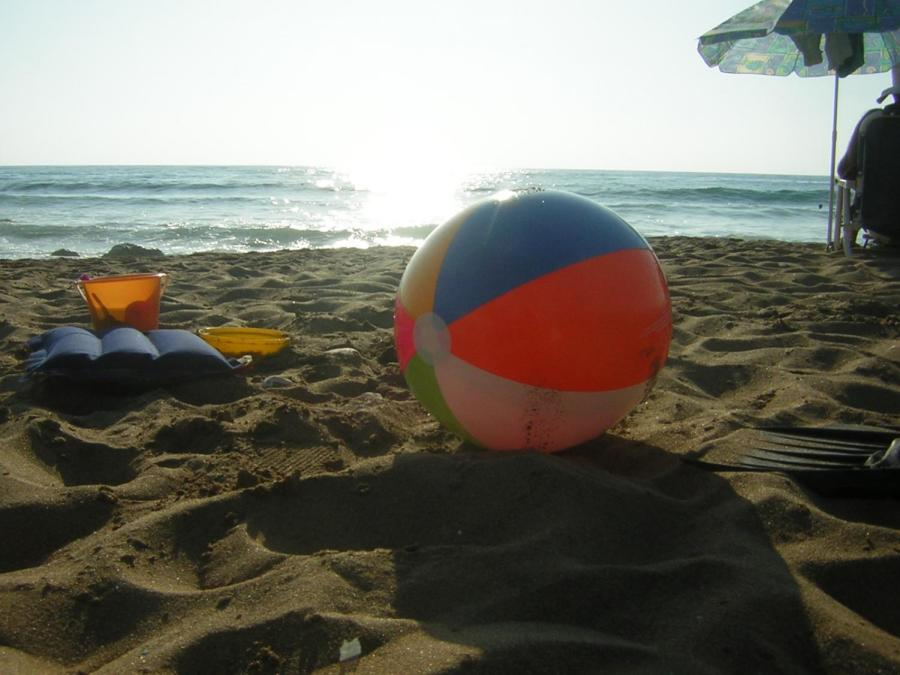 A+beach+ball+is+resting+peacefully+with+the+sun+behind+it+on+the+beach.