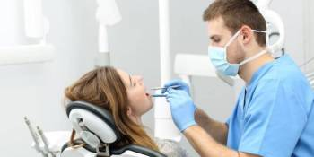 Dentist inspecting the teeth of a female patient