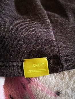 Close up of Grey T-shirt with Label showing a seam ripper and the word shit