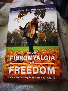 Book with words of From Fibromyalgia to Freedom with a woman walking through leaves