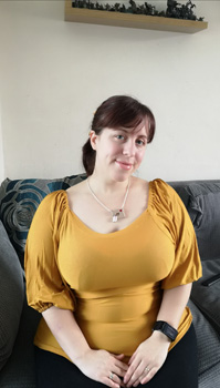 Sally Is Sat Down On A Grey Sofa With Her Hands Placed On Her Lap, Smiling At The Camera Wearing A Yellow Blouse And Sewing Machine Necklace