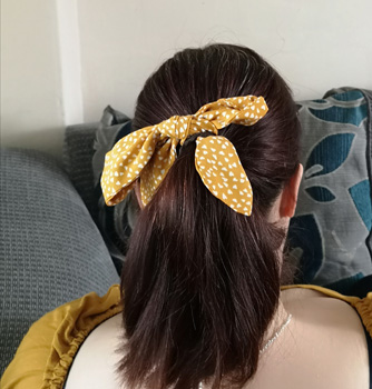 Back Of Sally's Head Tied In A Ponytail With A Yellow Hair Tie
