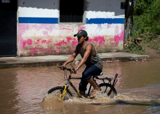 A man bikes down a street through receding floodwaters, two days after the passage of Hurricane Patricia (timesunion.com)