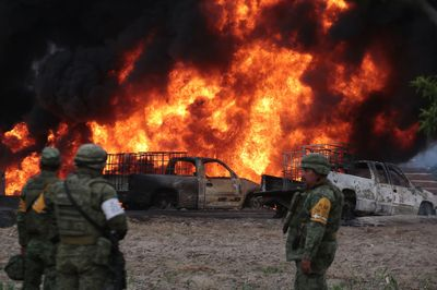 Soldiers stand in front of the flames generated by a fire in a clandestine fuel valve May 7. Photo: Jose Castanares/AFP via Getty Images