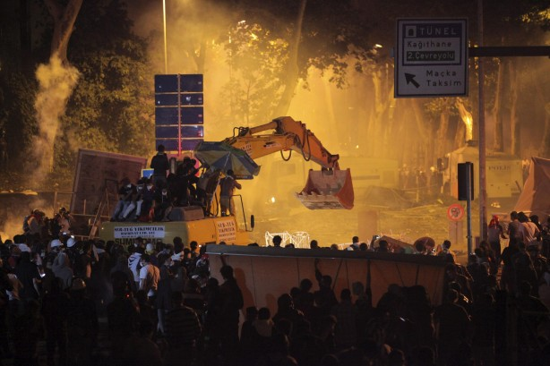 Anti-government protesters behind the barricades and on an excavator clash with riot police as they try to march to the office of Turkey's PM Erdogan in Istanbul