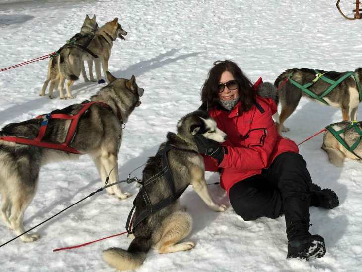 A happy Karin surrounded by the sled dogs.