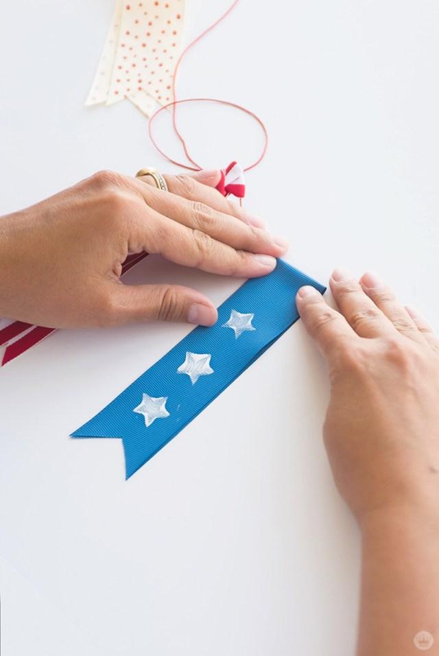 Gluing ribbon to a cord to make a July Fourth ribbon garland.