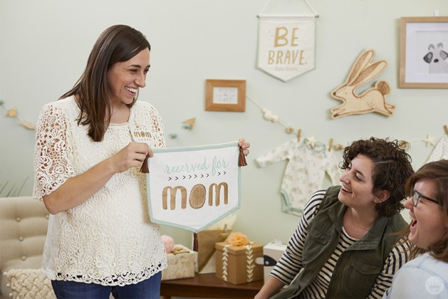 "Baby shower guests with ""reserved for Mom"" sign"
