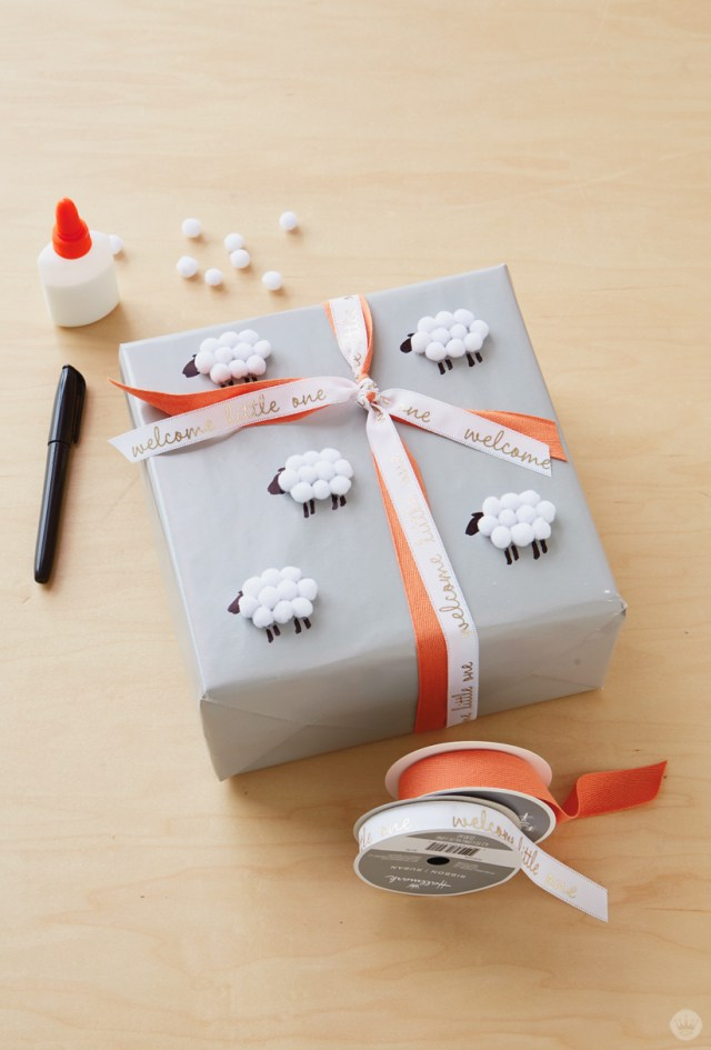 Supplies for covering a gift with sheep: glue, pom-poms, gift, ribbon, black marker.