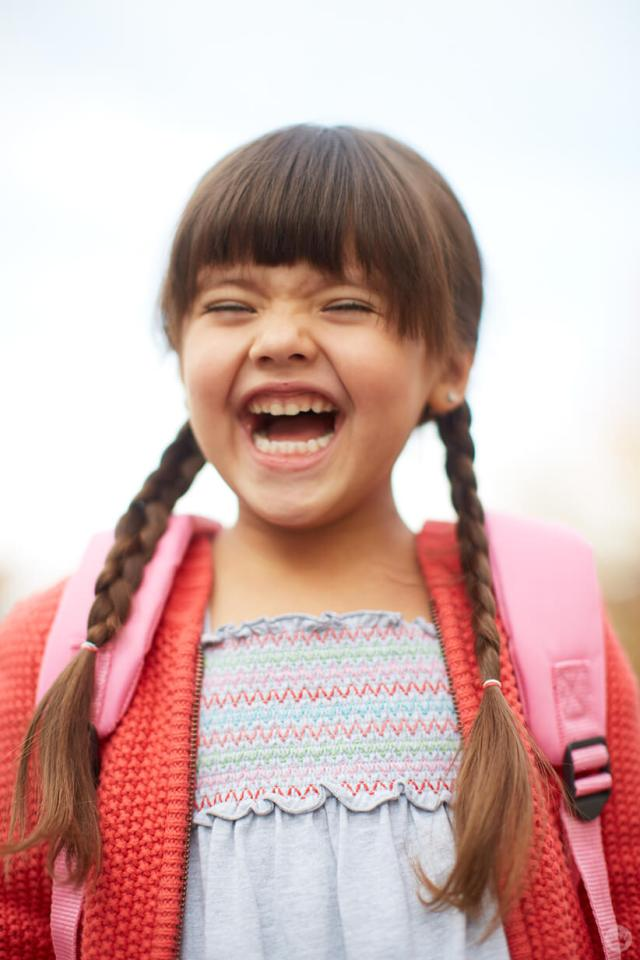 Back-to-school picture ideas: little girl laughing with her backpack on