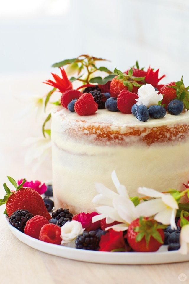 "Berries and flowers top a ""naked"" cake"