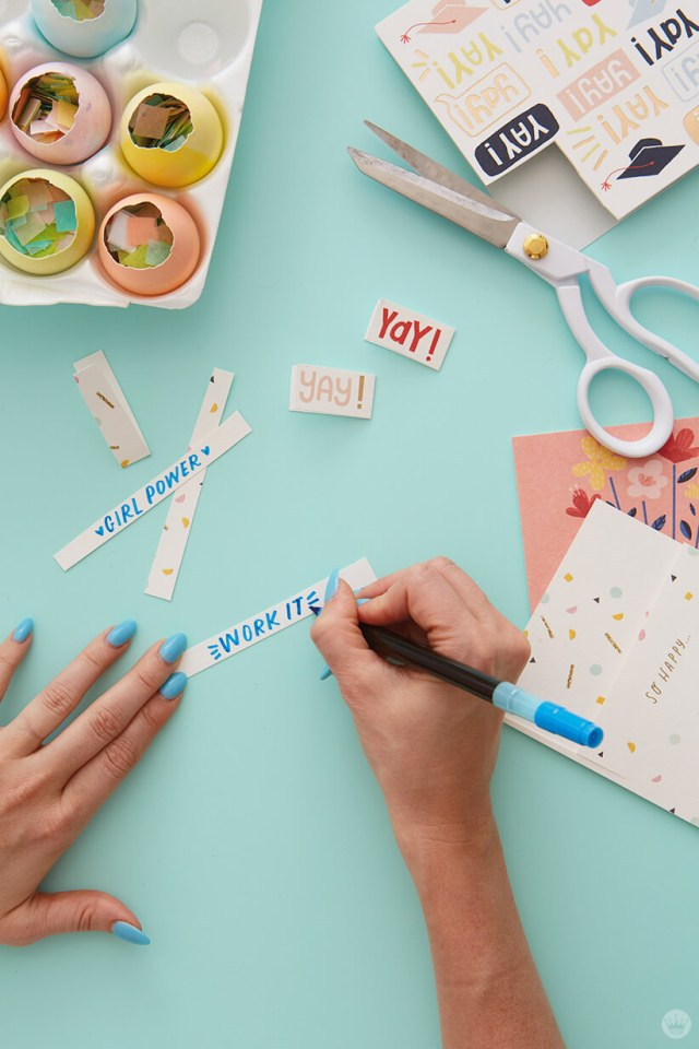 Writing messages on strips of paper for DIY cascarones | thinkmakeshareblog.com