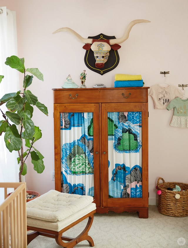 This children's room design features an armoire with patterned fabric insets and a hand-crafted longhorn sculpture.
