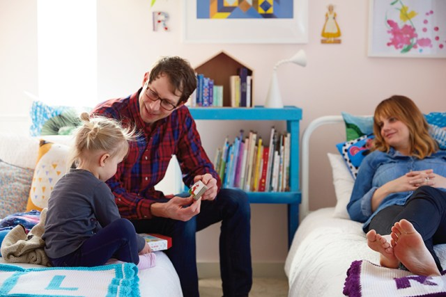 Dad and Mom sit on their girls' twin beds to read and play with their kids.