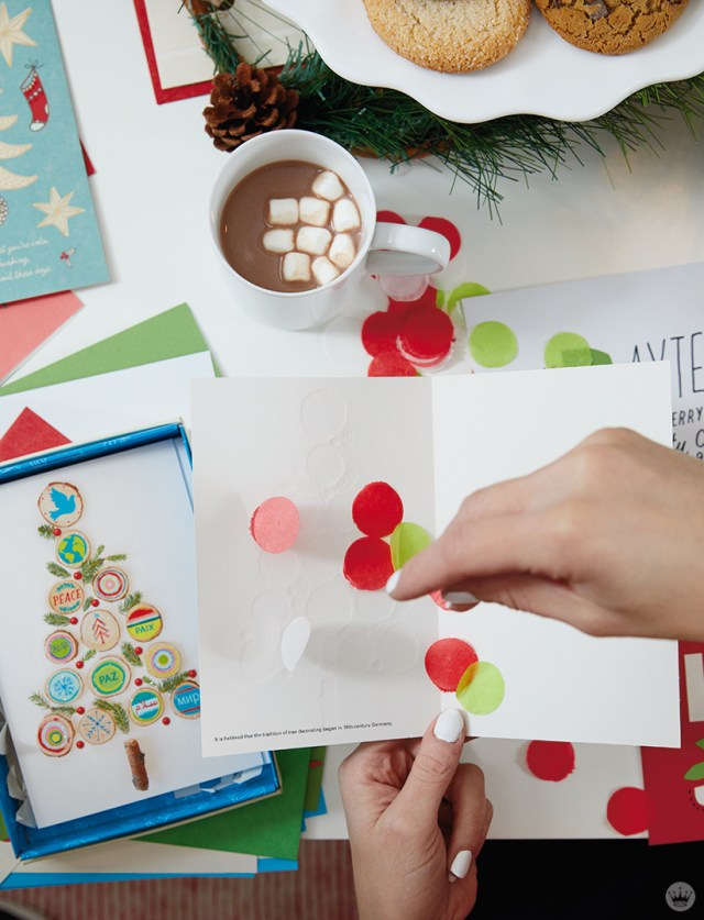 Sprinkling tissue paper confetti inside a holiday card