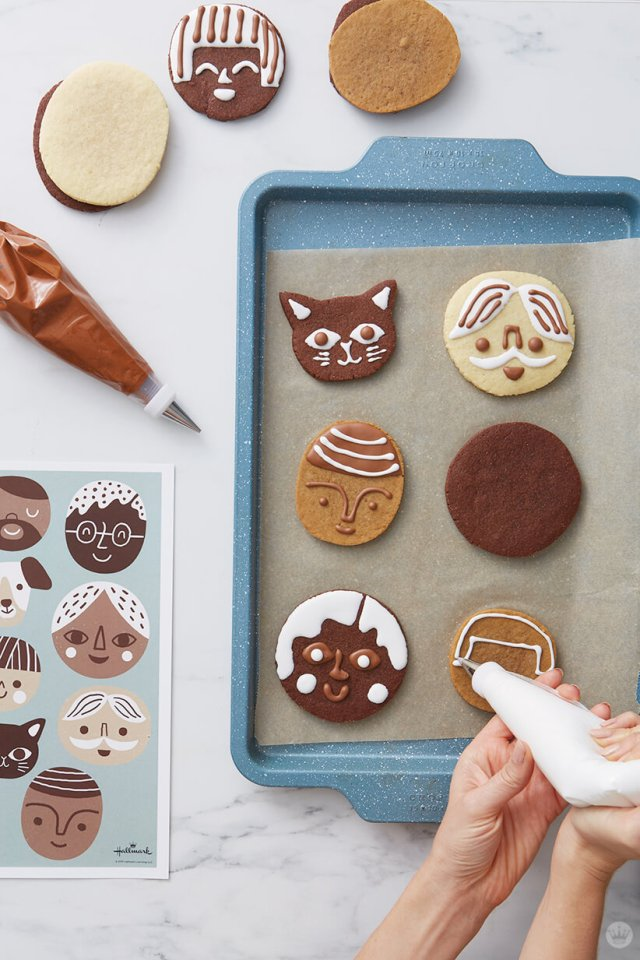 Decorating cookie faces with royal icing in a pastry bag | thinkmakeshareblog.com