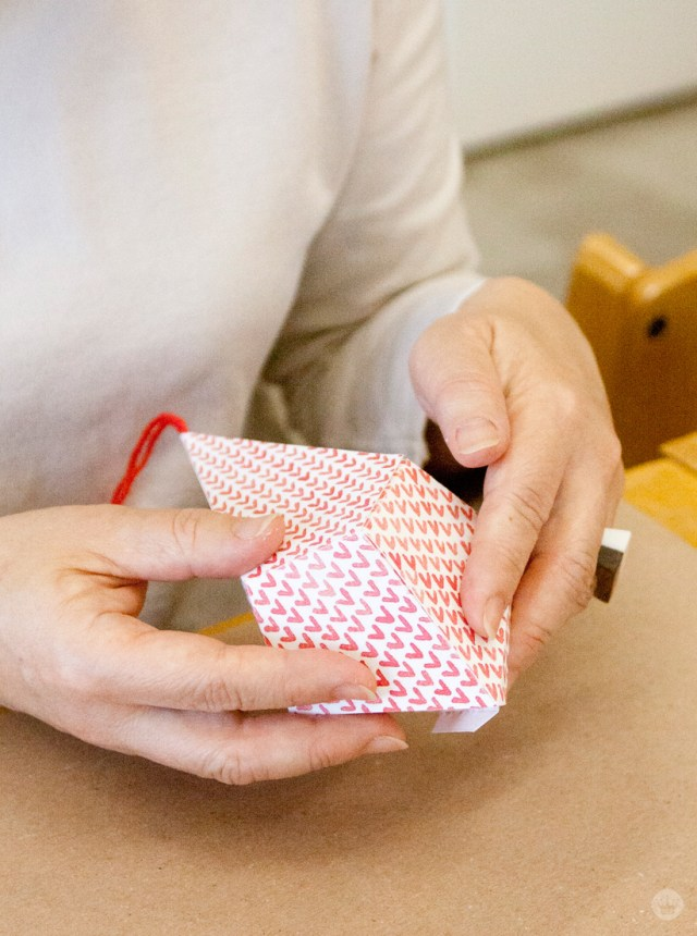 Folding your red and white patterned paper ornaments.