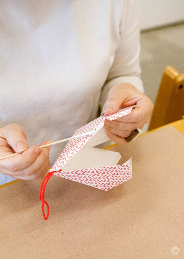 Gluing your red and white patterned paper ornaments for the Christmas tree.