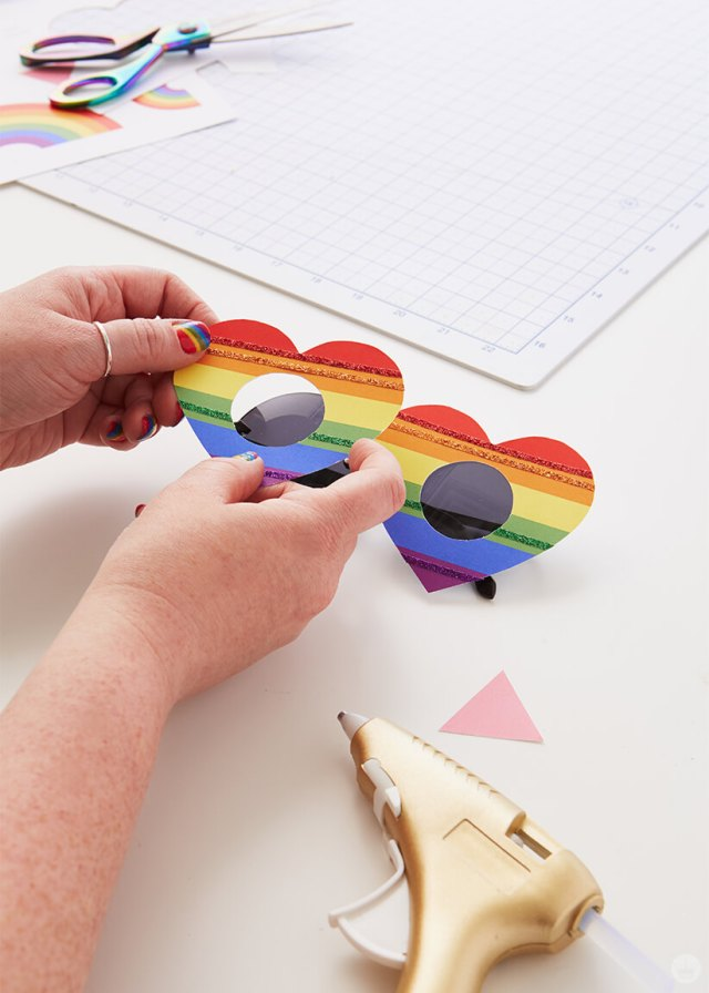 Attaching the template cutout hearts to the sunglasses for the DIY Pride Sunglasses | thinkmakeshareblog.com