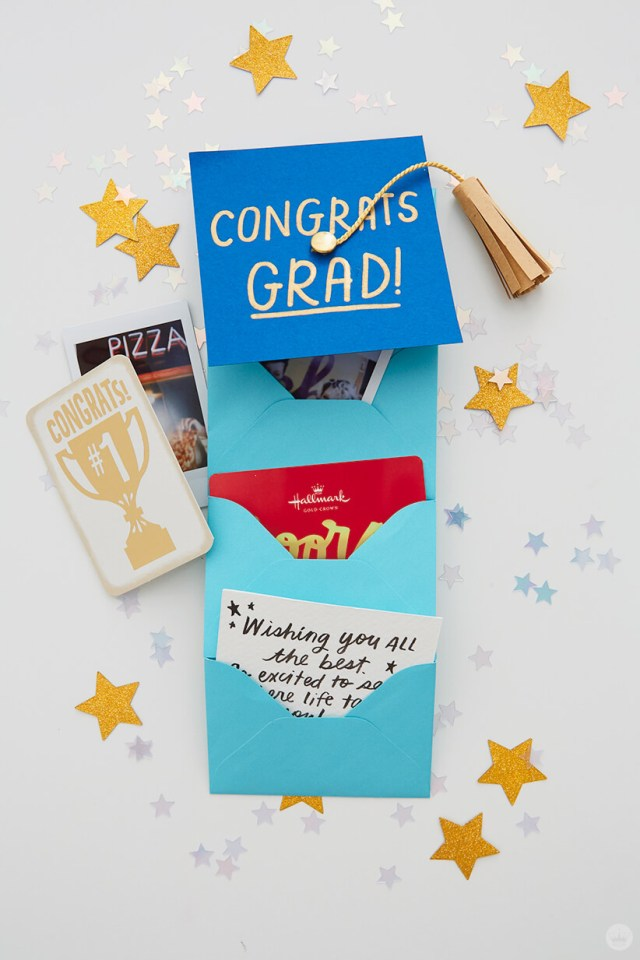 4 envelopes glued together with small gifts for the Mini Graduation Gift | thinkmakeshareblog.com