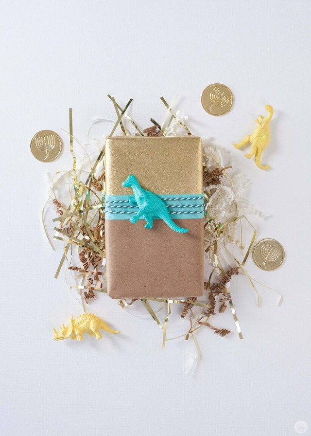 gift wrapped with a dinosaur toy on top | thinkmakeshareblog.com