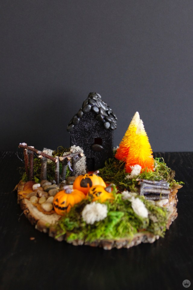 Miniature Haunted House Halloween decorations: One-story house with black paint and pebbled roof. Landscape includes candy-corn-color trees, wooden fence, jack o'lantern garden, and woodpile with hidden skull.