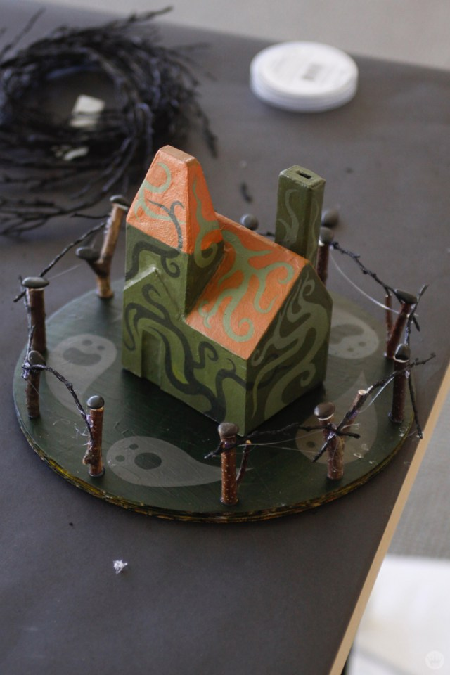 Mini haunted house painted green with an orange roof sits on a foundation decorated with ghosts, surrounded by a wooden fence.