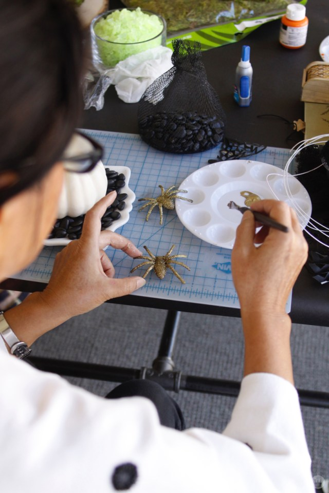 Miniature Haunted House Halloween decorations: Artist painting plastic spiders in glittery gold.