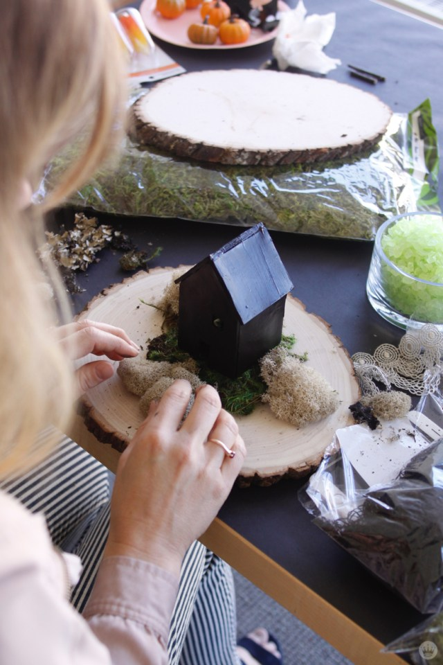 Miniature Haunted House Halloween decorations: Artist adding moss to a tiny black house on a slice of tree-stump.