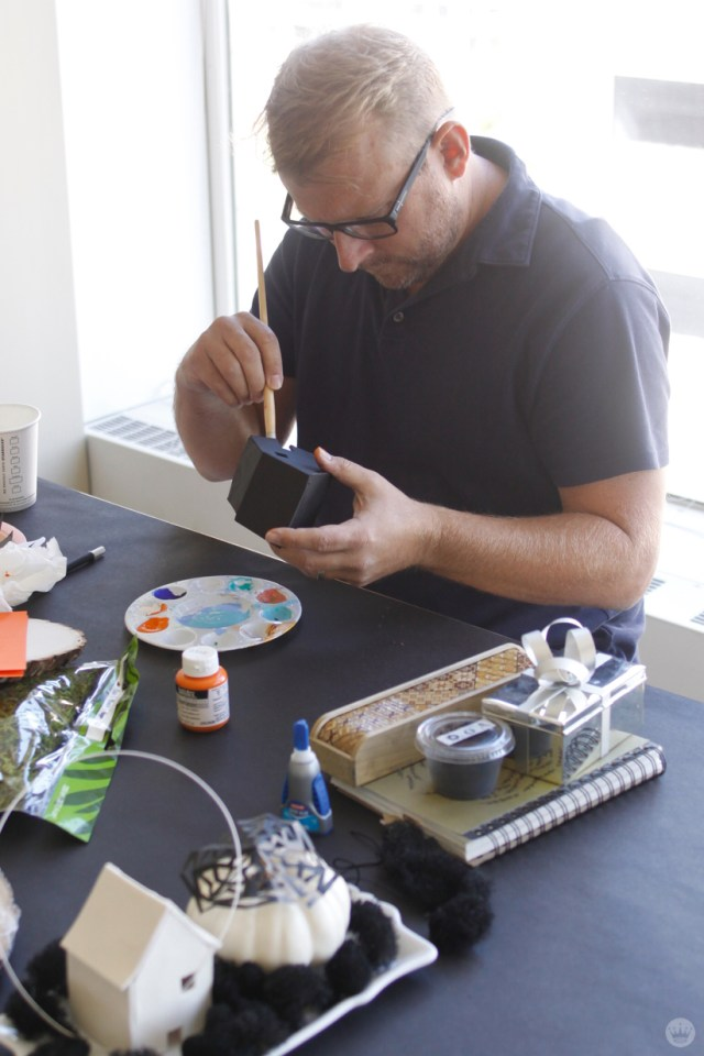Artist painting a miniature clay house black.