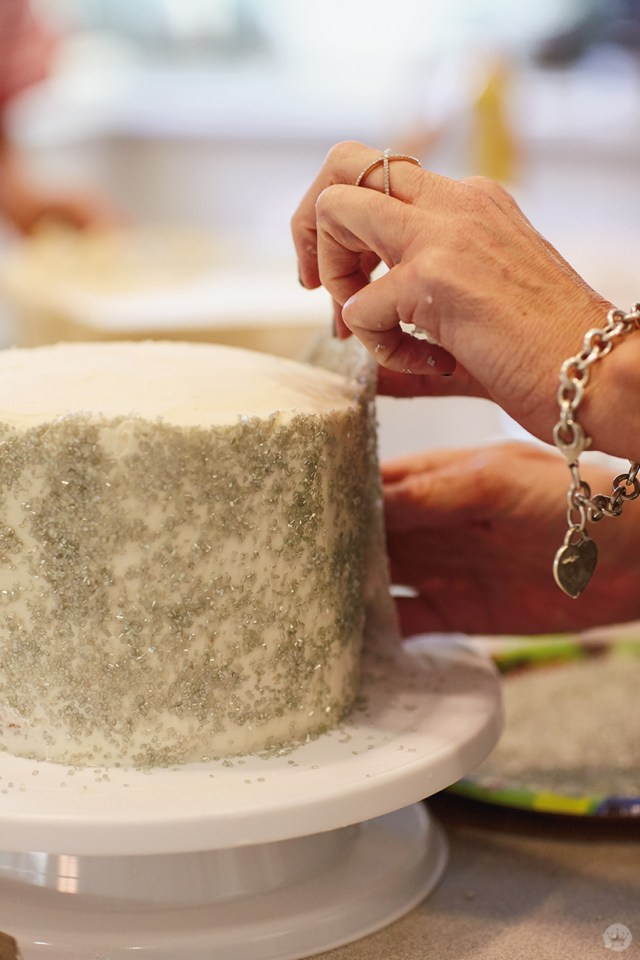 Using wax paper to apply coarse sanding sugar to a frosted layer cake